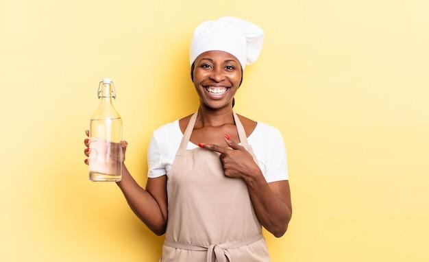 Femme chef afro noire à l'air excitée et surprise pointant vers le côté et vers le haut pour copier l'espace tenant une bouteille d'eau