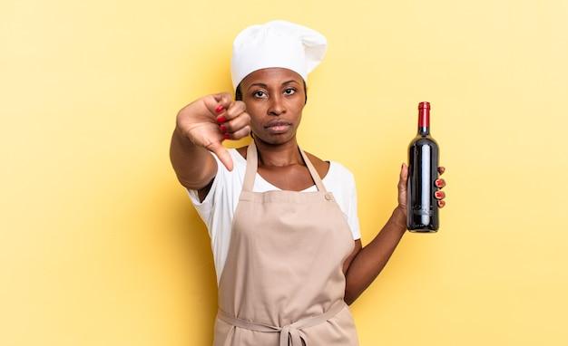 Femme chef afro noire se sentant fâchée, en colère, agacée, déçue ou mécontente, montrant les pouces vers le bas avec un regard sérieux. concept de bouteille de vin