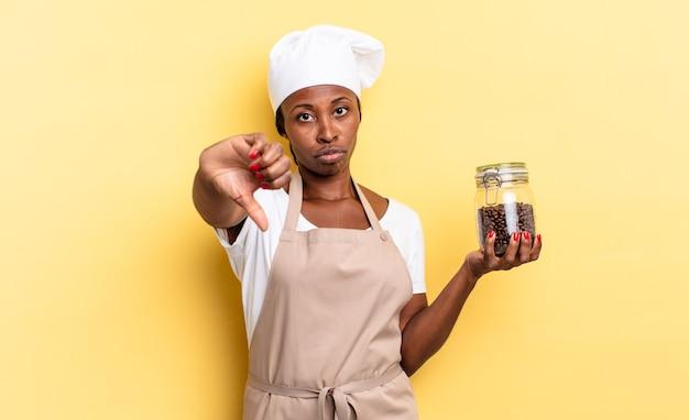 Femme chef afro noire se sentant fâchée, en colère, agacée, déçue ou mécontente, montrant les pouces vers le bas avec un regard sérieux. concept de grains de café