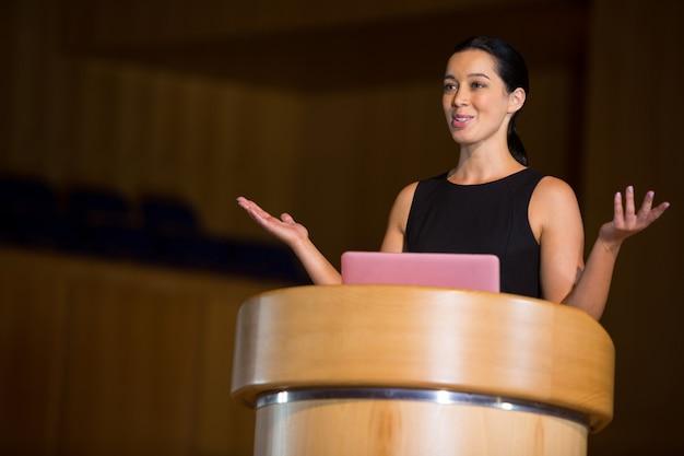 Femme chef d'entreprise donnant un discours au centre de conférence