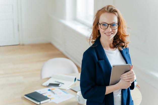Femme chef d'équipe de travail détient une tablette numérique