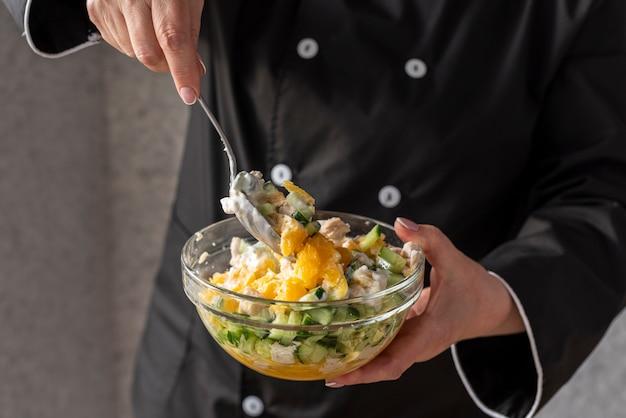 Femme chef mélange des ingrédients dans un bol