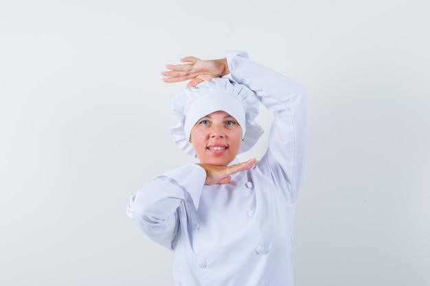 Femme chef montrant le geste de danse en uniforme blanc et à la recherche de charme.