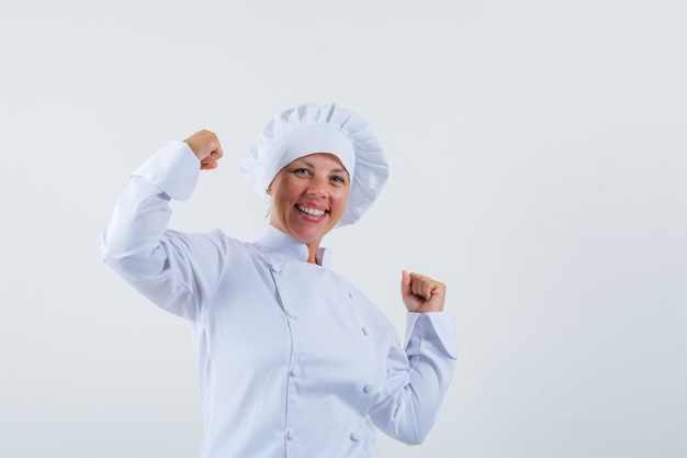 Femme chef montrant le geste du gagnant en uniforme blanc et à la joyeuse.