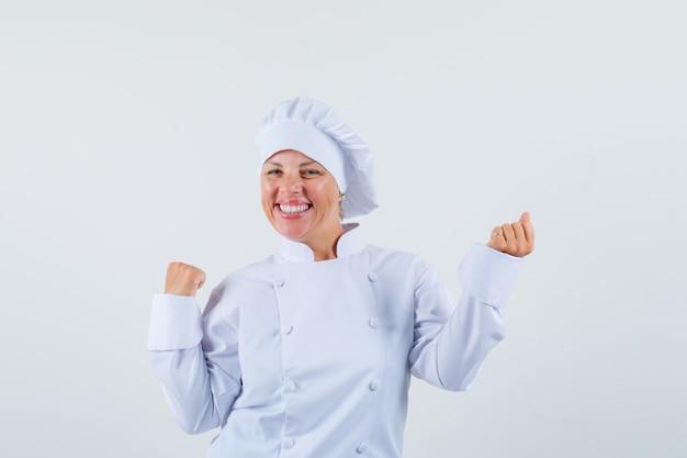 Femme chef montrant le geste gagnant en uniforme blanc et à la joyeuse.