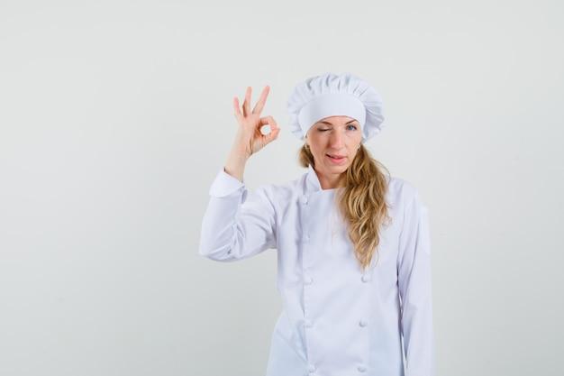 Femme chef montrant signe ok et clignant des yeux en uniforme blanc