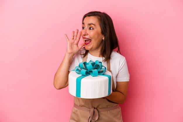 Femme de chef pâtissier d'âge moyen tenant un gâteau isolé sur fond bleu criant et tenant la paume près de la bouche ouverte.