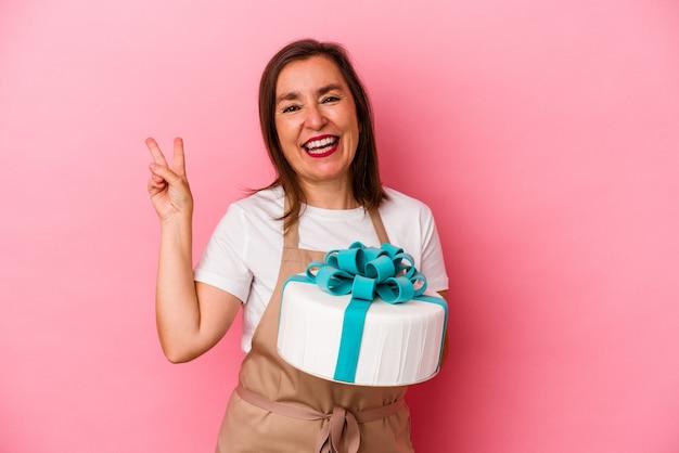 Femme de chef pâtissier d'âge moyen tenant un gâteau isolé sur fond bleu joyeux et insouciant montrant un symbole de paix avec les doigts.