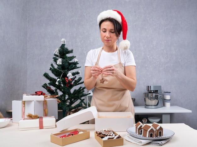 Femme chef pâtissier emballe des cadeaux avec des bonbons de noël. biscuits au gingembre.