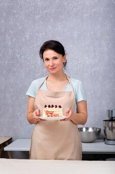 Femme de chef pâtissier tient un gâteau aux fruits rouges.