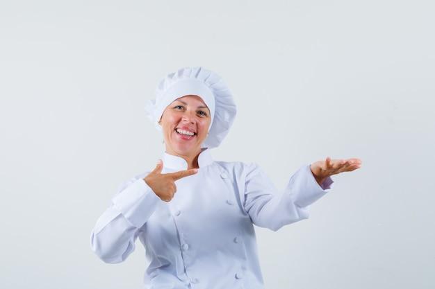 Femme chef pointant vers sa main gauche tout en tenant quelque chose en uniforme blanc et à l'optimiste.