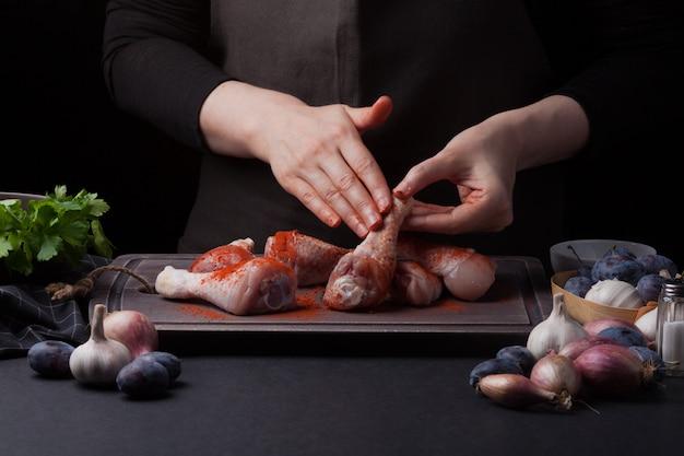 Une femme chef prépare un poulet.