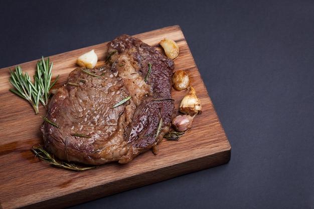 La femme chef prépare un steak de bœuf.