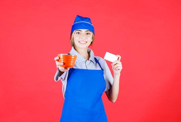 Femme chef en tablier bleu tenant une tasse de nouilles en céramique orange et présentant sa carte de visite