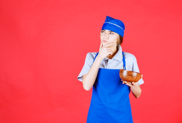 Femme chef en tablier bleu tenant une tasse de nouilles en cuivre chinois et pensant