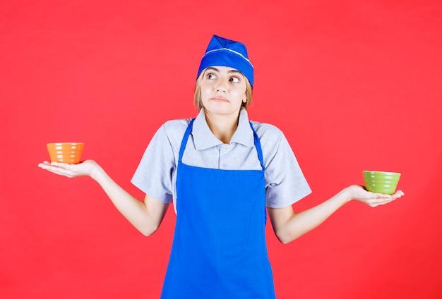 Femme chef en tablier bleu tenant des tasses de nouilles en céramique orange et verte et réfléchissant à la façon de les utiliser