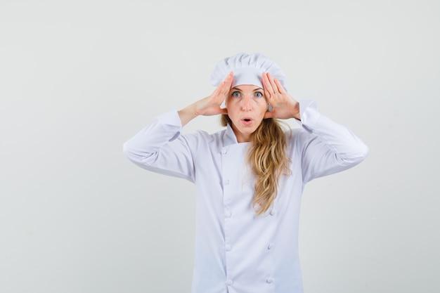 Femme chef tenant la main sur la tête pour voir clairement en uniforme blanc et à la recherche