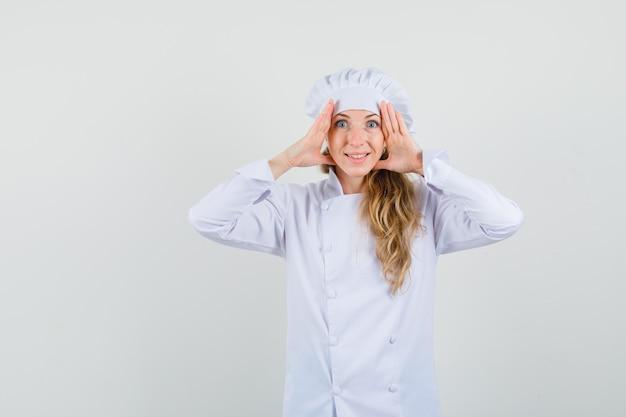 Femme chef tenant la main sur la tête pour voir clairement en uniforme blanc et à la surprise