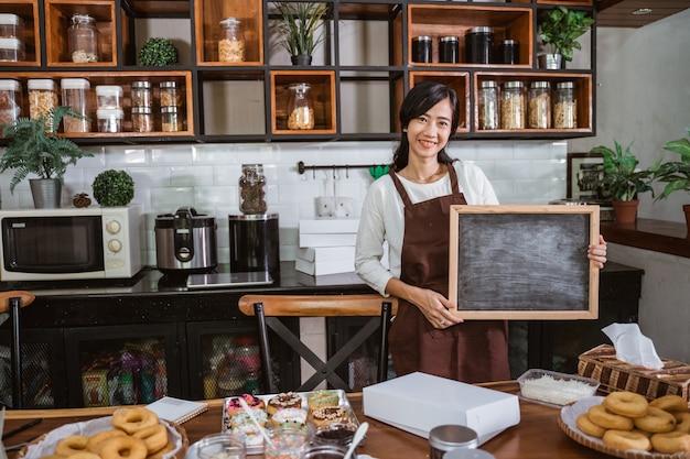 Femme chef tenant un tableau noir en se tenant debout dans la salle de cuisine