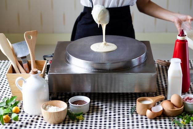 Femme chef verser portion de pâte liquide à la main avec une louche sur la table de cuisson électrique pour la cuisson des crêpes, des crêpes.
