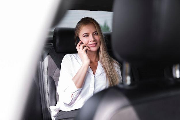 Femme en chemise blanche assise dans la voiture et parlant au téléphone