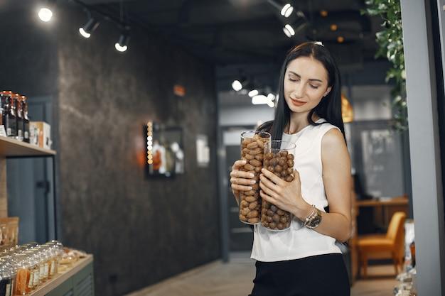 Femme en chemise blanche au supermarché. brunette regarde la caméra et sourit.