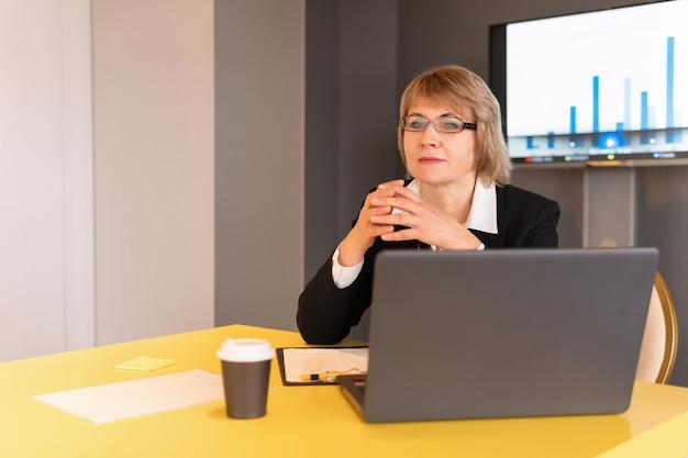 Une femme en chemise blanche entraîne des auditeurs dans la salle d'affaires