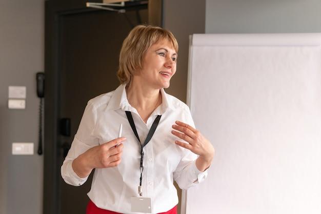 Une femme en chemise blanche entraîne des auditeurs dans la salle des affaires.