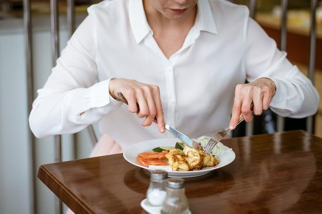 Une femme en chemise blanche est assise à une table en train de manger avec un couteau et une fourchette dans ses mains