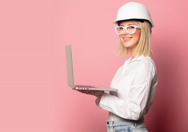 Femme en chemise blanche, lunettes et casque avec ordinateur portable