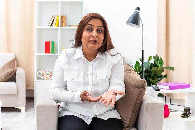 Femme en chemise blanche et pantalon noir avec une expression confuse levant les bras d'indignation assis sur la chaise dans un salon lumineux