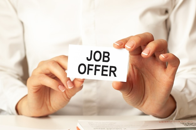 Une femme en chemise blanche tient une feuille de papier avec le texte : offre d'emploi. concept d'entreprise pour les entreprises