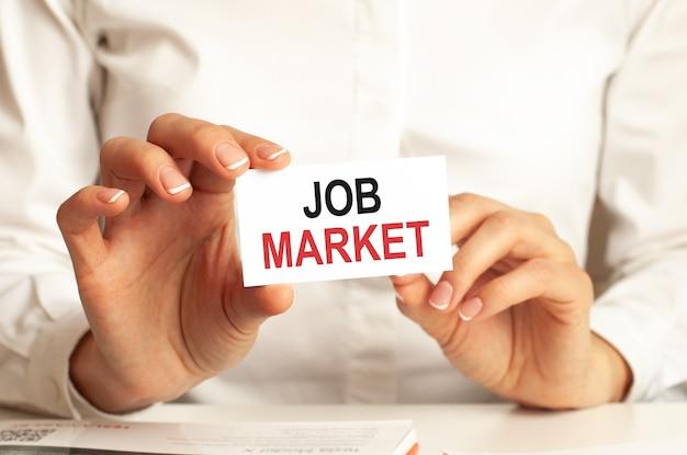 Une femme en chemise blanche tient un morceau de papier avec le concept d'entreprise du marché du travail pour les entreprises
