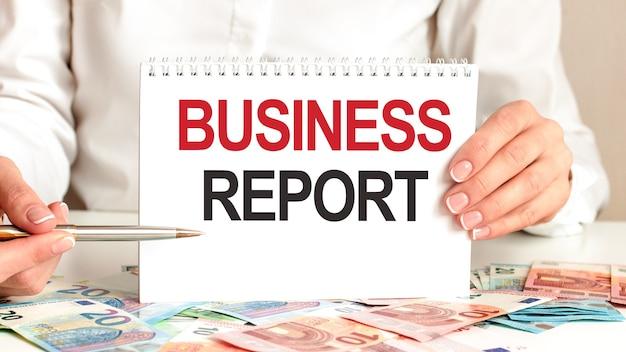 Une femme en chemise blanche tient un morceau de papier avec le texte: rapport d'activité. marqueurs multicolores et tablette sur une table. concept d'entreprise pour les entreprises et les établissements d'enseignement.