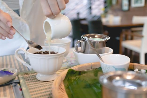 Femme en chemise blanche verse du lait dans une tasse de café chaud.