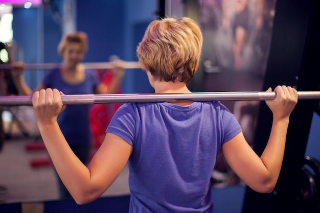 Femme en chemise bleue et cheveux courts avec haltères sur les épaules dans la salle de gym. concept de personnes, de remise en forme et de santé
