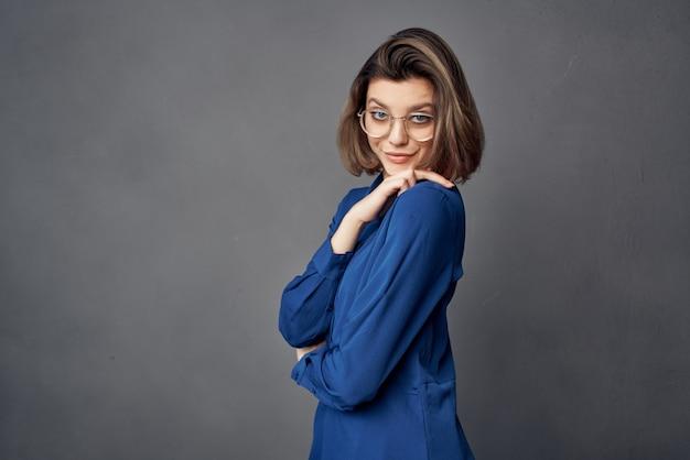 Femme en chemise bleue lunettes de style élégant posant la mode