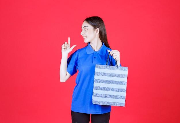 Femme en chemise bleue tenant un sac à provisions à rayures bleues.