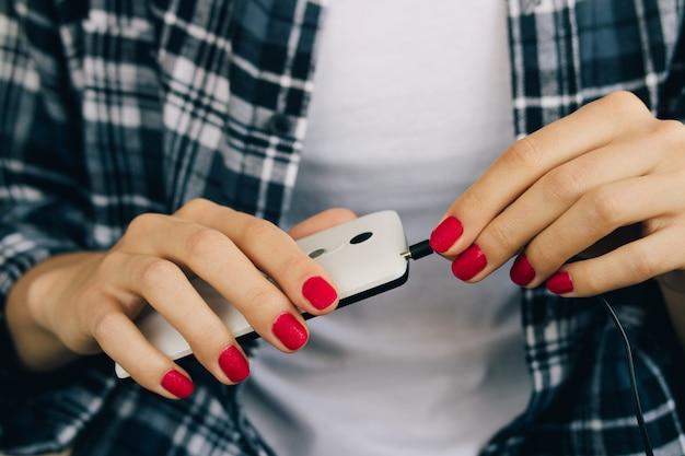 Femme en chemise à carreaux et manucure rouge connecte un casque au téléphone mobile blanc
