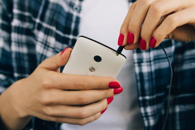 Femme en chemise à carreaux et manucure rouge connecter des écouteurs au gros plan de téléphone mobile blanc