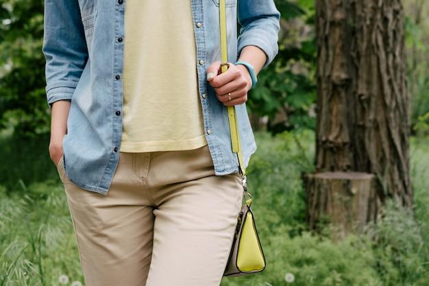 Femme en chemise de denim et un t-shirt jaune et un pantalon marchant sur le parc verdoyant au printemps