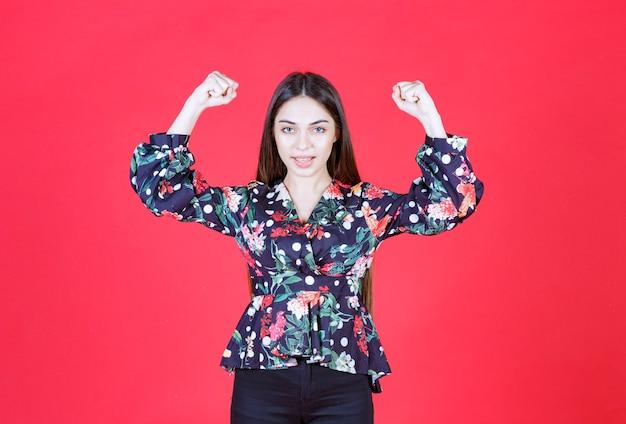 Femme en chemise florale debout sur un mur rouge et démontrant les muscles de ses bras.