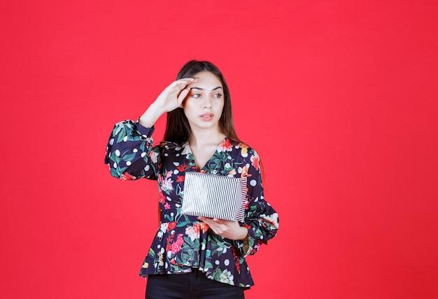 Femme en chemise florale tenant une boîte-cadeau en argent et a l'air réfléchie.