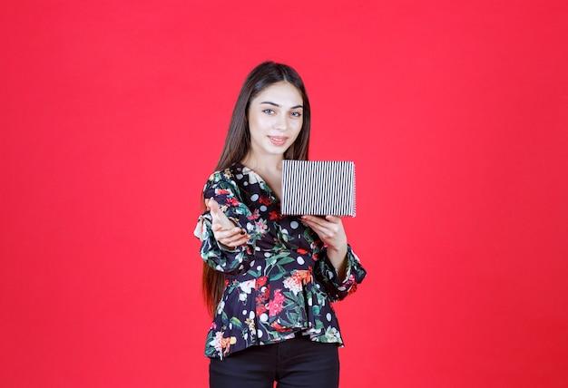 Femme en chemise florale tenant une boîte-cadeau en argent et invitant quelqu'un à s'en occuper.