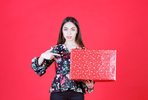 Femme en chemise florale tenant une boîte-cadeau rouge avec des points blancs dessus.