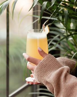 Femme en chemise d'hiver avec un verre de jus d'ananas par la fenêtre.