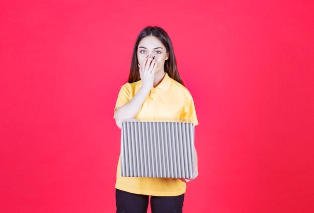 Femme en chemise jaune tenant une boîte-cadeau en argent et semble confuse et réfléchie.
