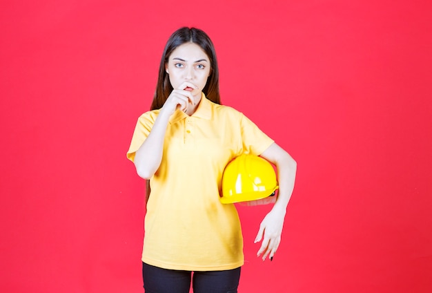 Femme en chemise jaune tenant un casque jaune et semble confuse et réfléchie.