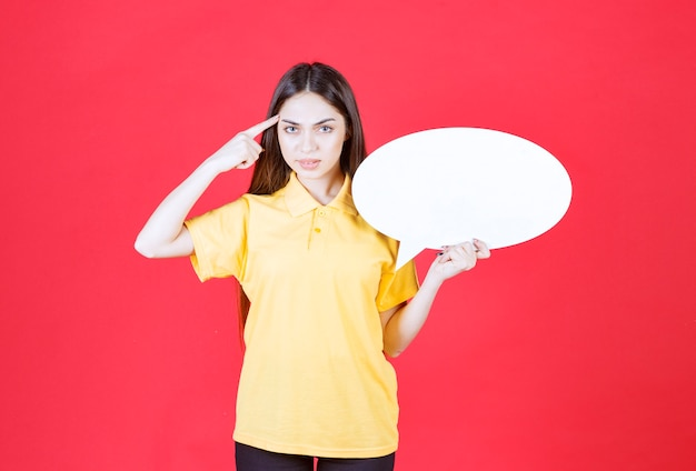 Femme en chemise jaune tenant un panneau d'information ovale et ayant une bonne idée.