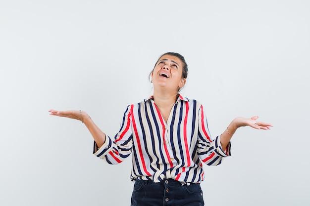 Femme en chemise, jupe écartant les paumes de côté tout en levant les yeux et à la reconnaissance